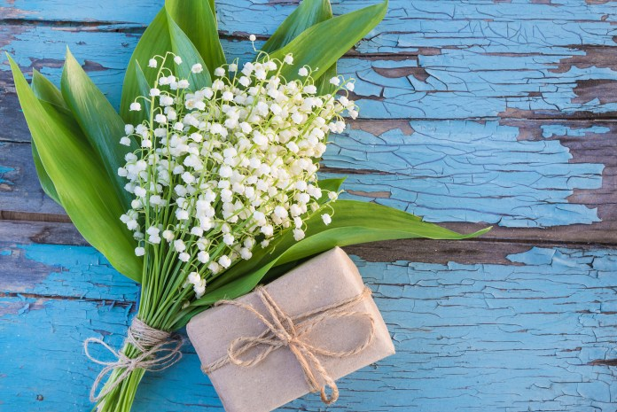 Bouquet of lilies of the valley and handmade gift box on blue old paint wooden background.