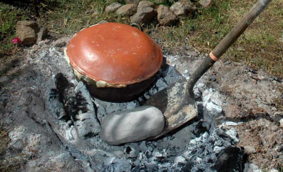 Tamales and mushrooms cooking in hot coals.