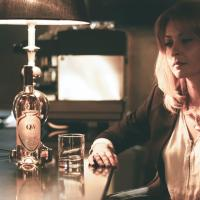 pensive young woman drinking alcohol beverage in bar