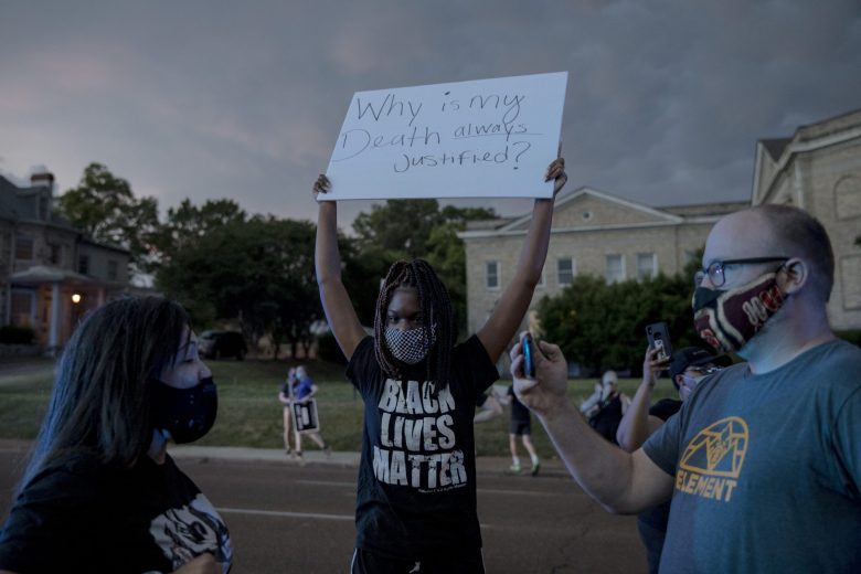 """A scene from a demonstration. A white man, wearing a mask and dark t-shirt, films a Black woman on his cell phone as another Black woman holds a sign in the background. The sign reads """"Why is my death always justified?"""""""