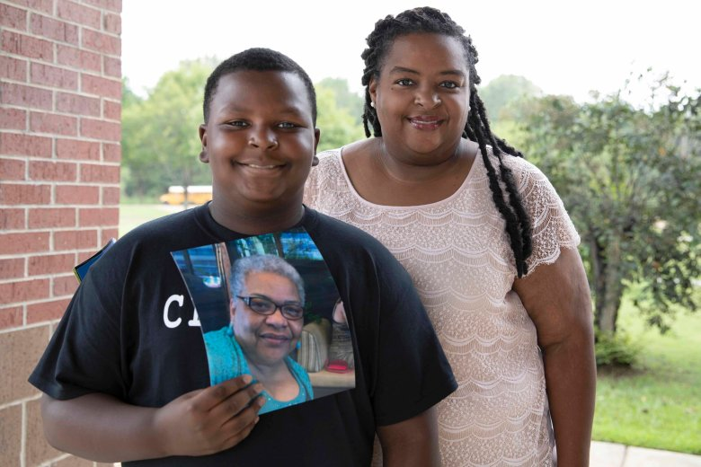 K arlton Jackson (left), age 10, holds a photo of his late grandmother, Carol Faye Doby, as he stands with his mother Shenika Jackson (right) on Friday, September 25, 2020 in Bolton, MS. Doby, of Stonewall, passed away from complications of COVID-19 earlier this year.   Sarah Warnock/MCIR