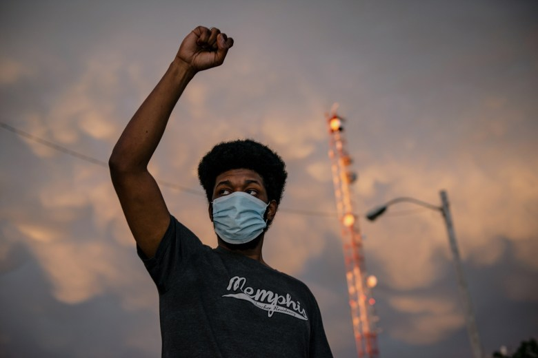 A man raises his fist during protest.