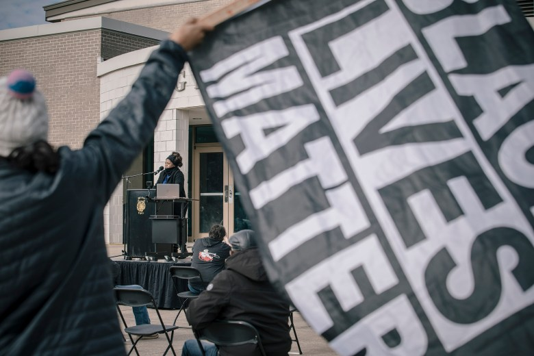 Kizzy Jones (background) stands at a podium during a rally against the Byhalia Connection Pipeline as someone holds a Black Lives Matter flag in the foreground.