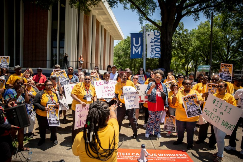 A group of people hold signs demanding a better wage from the University of Memphis.