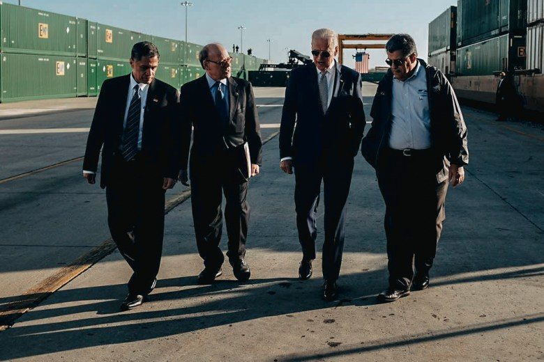 President-elect Joe Biden walks with three other men between railroad cars at an intermodal facility in Memphis.