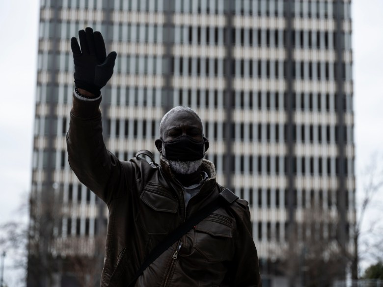A Black man wearing a face mask holds a hand in the air after a march.