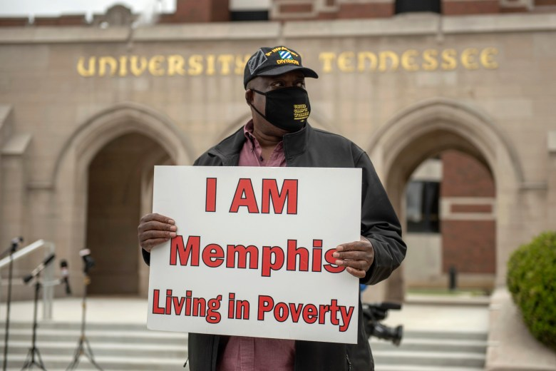"""Michael Garrett, a laid-off UTHSC craftsman, holds a sign that says """"I AM Memphis Living in Poverty."""""""