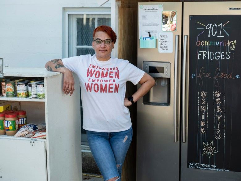 An image LJ Abram, wearing jeans and a t-shirt, standing next to one of her group's first community refrigerators.