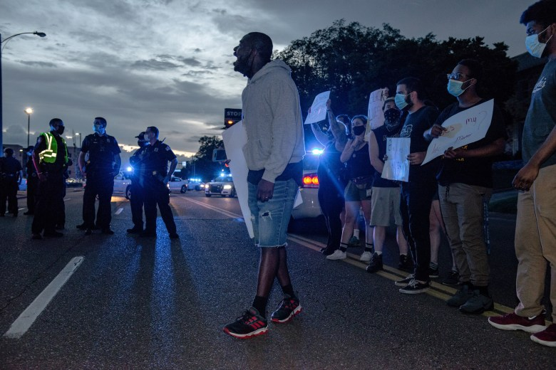 Demonstrators stand in the street as they protest the killing of Black people.