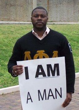 William E. Arnold Jr. wearing an Alpha Phi Alpha sweater and holding an I Am A Man sign.