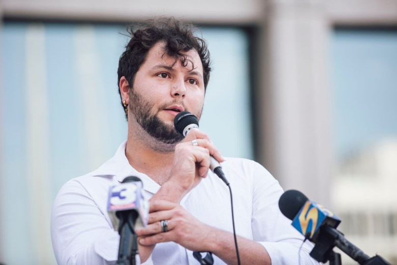 Jackson Beck holds a microphone and speaks before an audience at the Memphis and Shelby County Moral Budget Coalition rally.