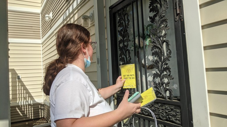 A woman leaves a yellow pamphlet about coronavirus vaccination between on a door in South Memphis.