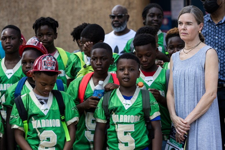 Shelby County District Attorney Amy Weirich stands next to a group of young Black boys who are members of the South Memphis Warriors Youth Football Organization.