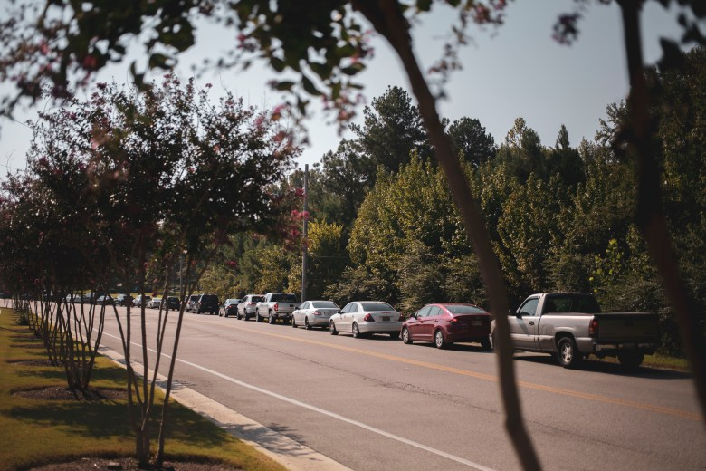 Cars queue along Callis Cutoff Road as people wait for a COVID-19 test.