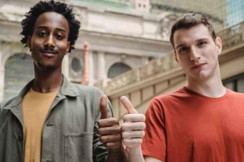 positive young multiracial guys demonstrating thumbs up sign at camera