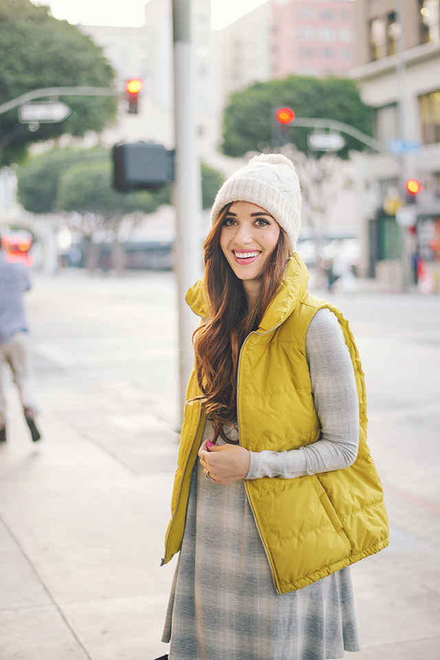 yellow puffy vest with beanie and gray dress by M Loves M