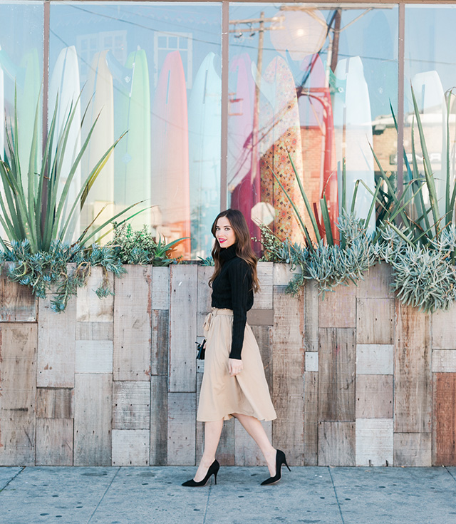 black turtleneck with beige skirt and black hee