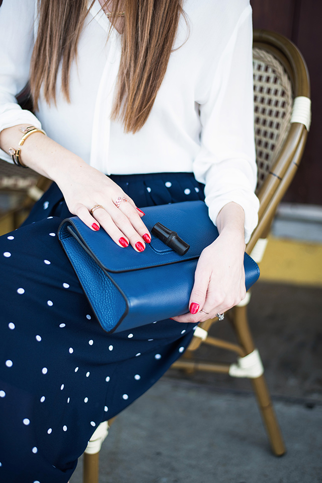 blue gucci shoulder bag with white blouse and navy skirt