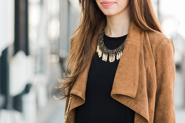 brown suede jacket with a gold statement necklace