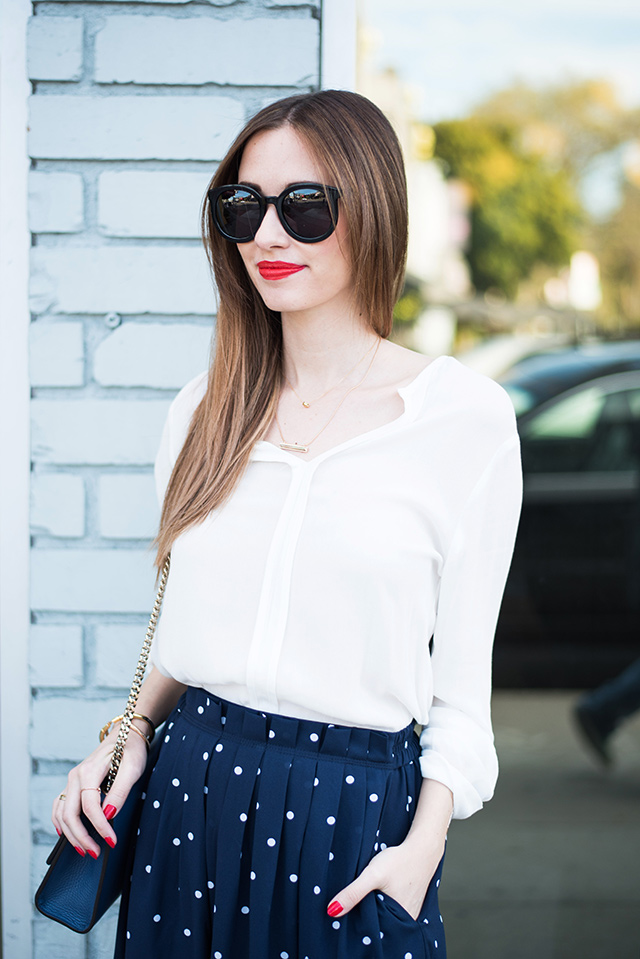 white blouse with a navy polka dotted skirt and red lipstick