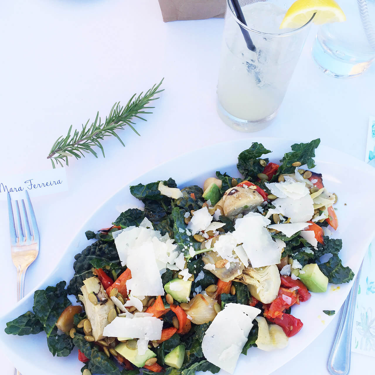 a delicious kale and avocado salad with artichoke hearts, carrots, and parmesan