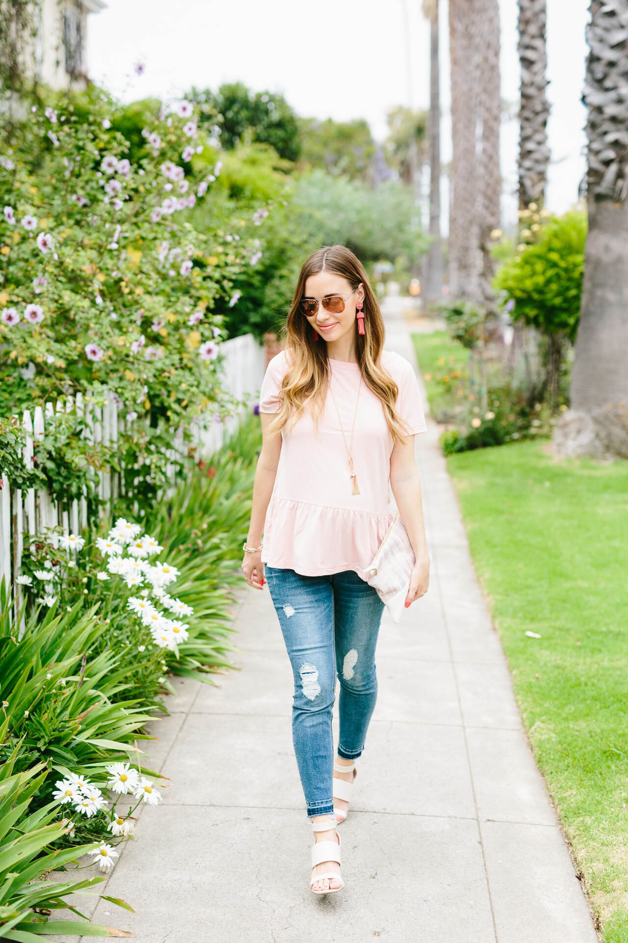 a casual outfit with pink peplum top and distressed jeans