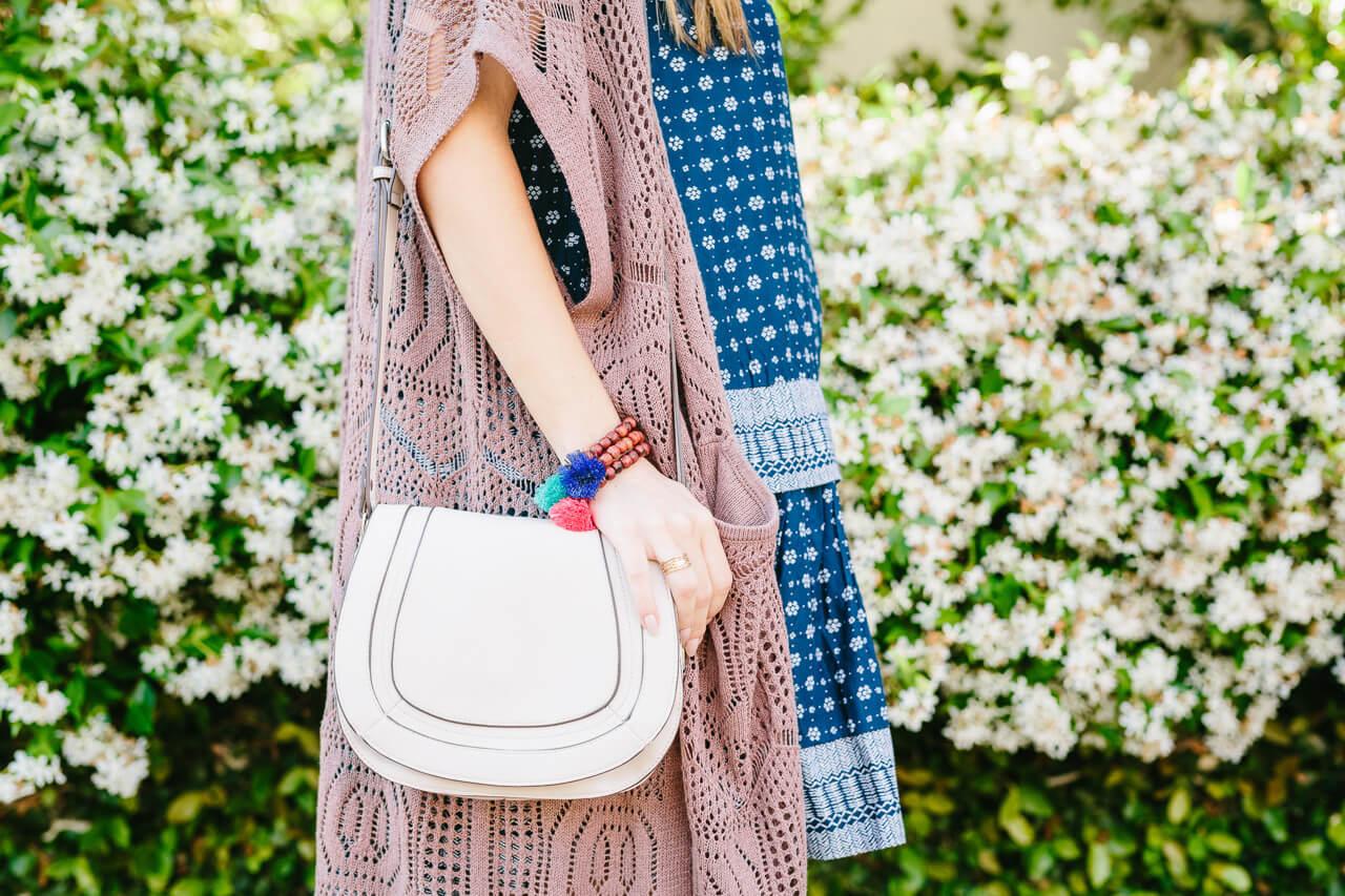 an off-white saddle bag with tassel bracelets