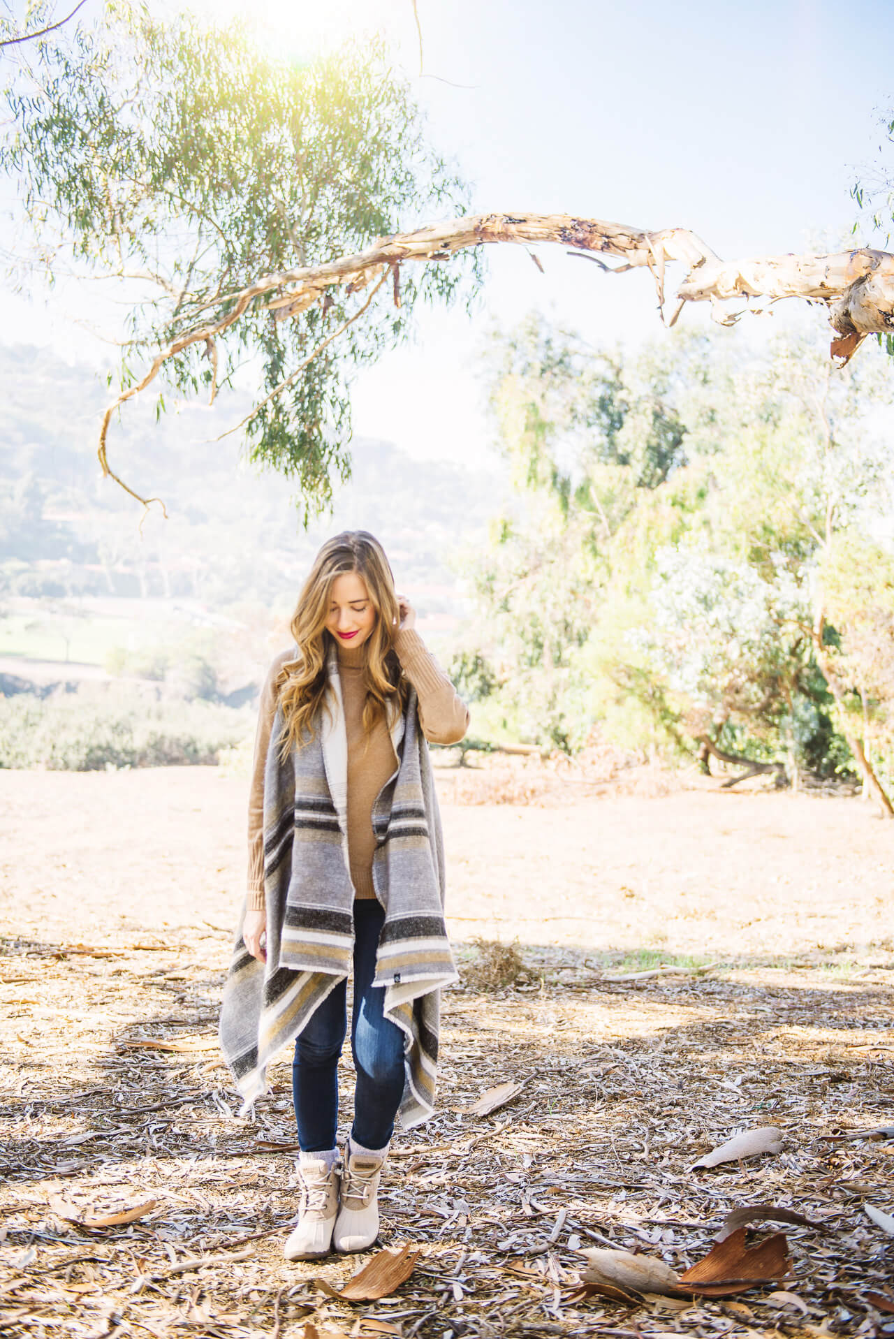 striped poncho with jeans and duck boots