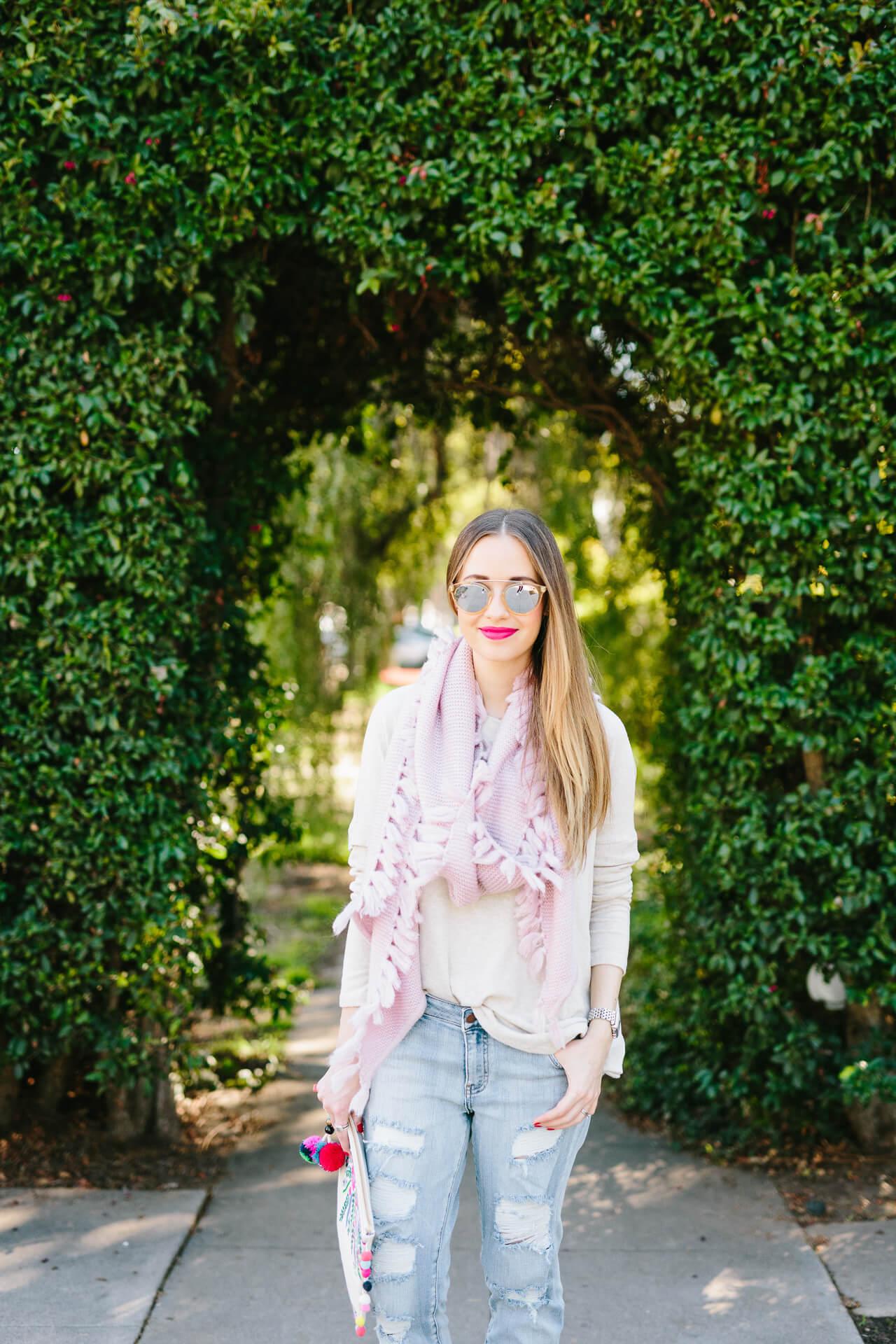 cream sweater with pink tassel scarf