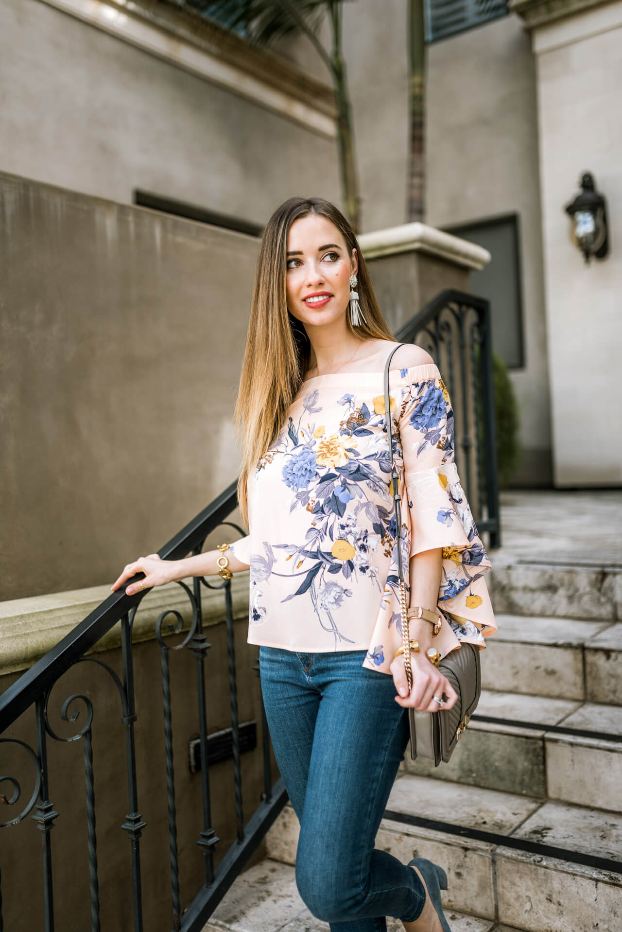 a pretty floral top with tassel earrings and jeans