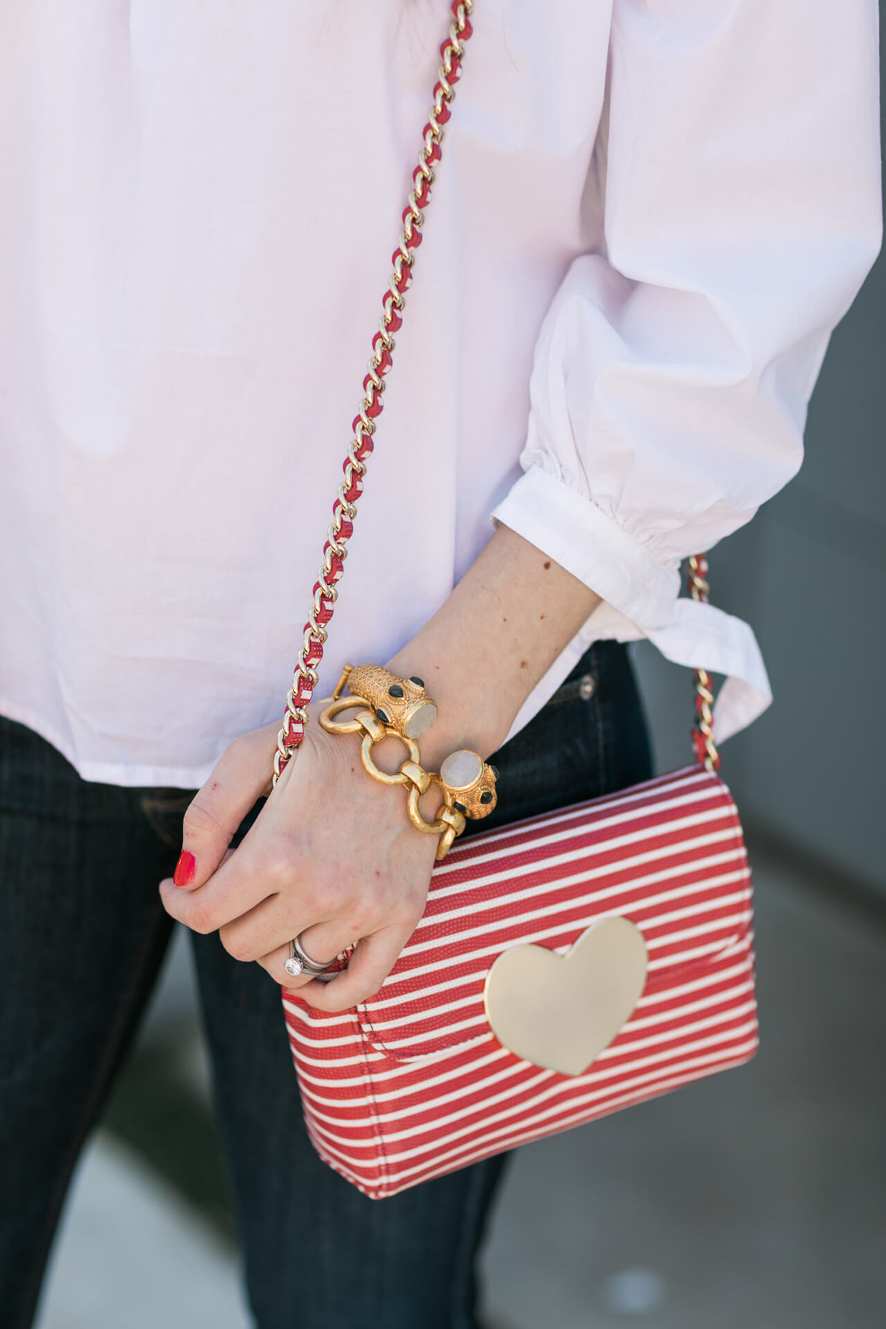 a striped chain bag with gold heart