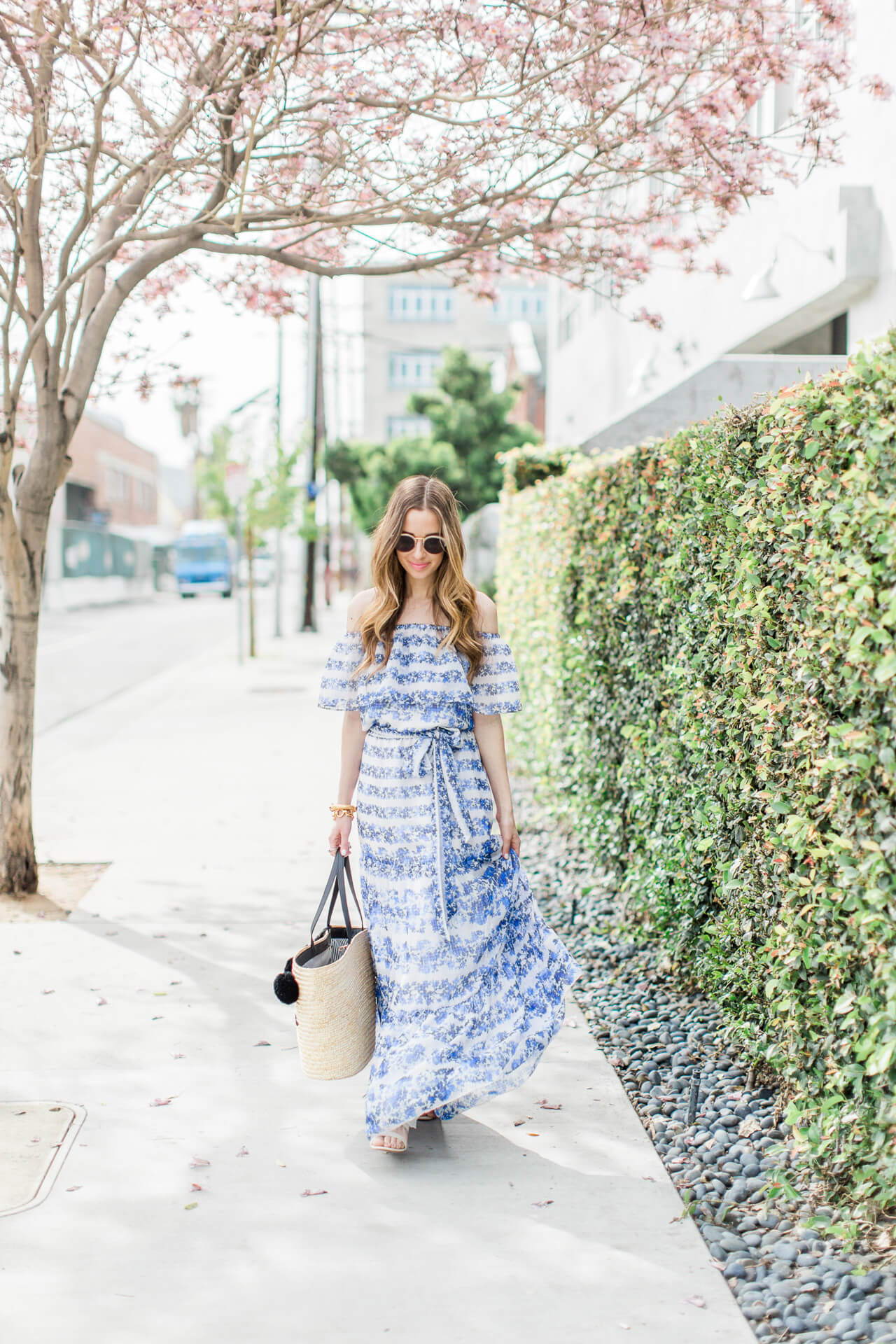 a feminine blue and white floral maxi dress with straw tote