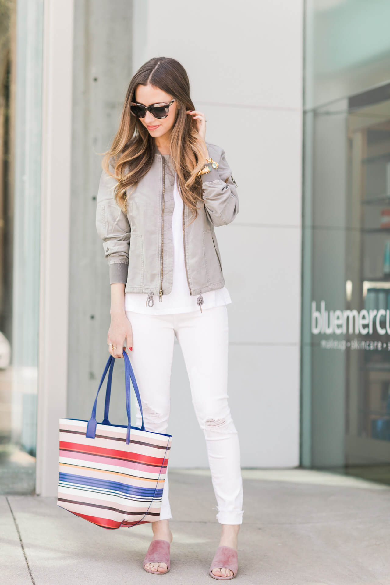 white outfit with gray bomber jacket and striped tote bag