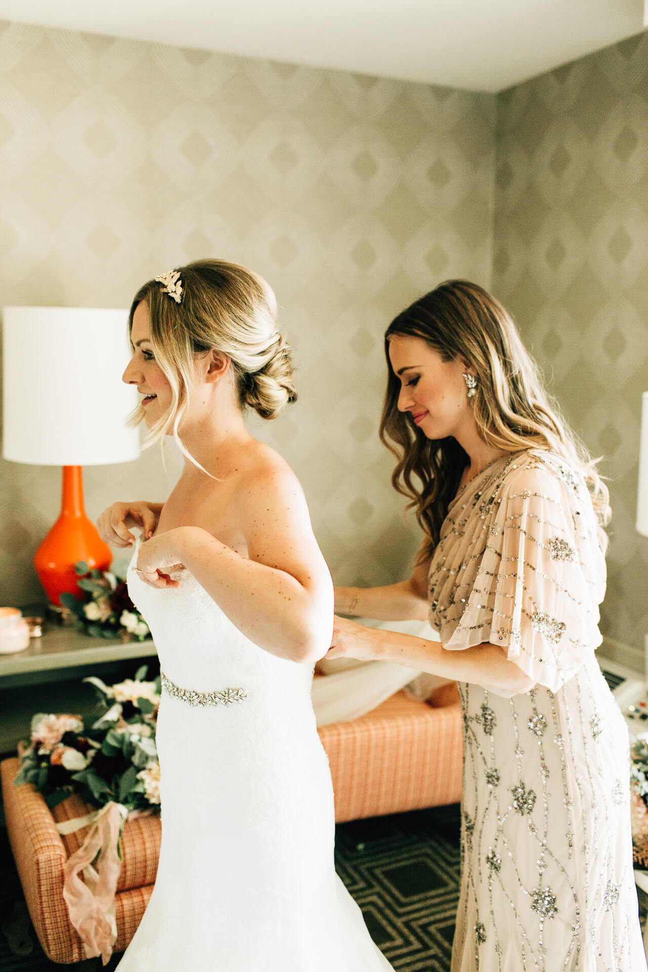 helping the bride get dressed on her wedding day