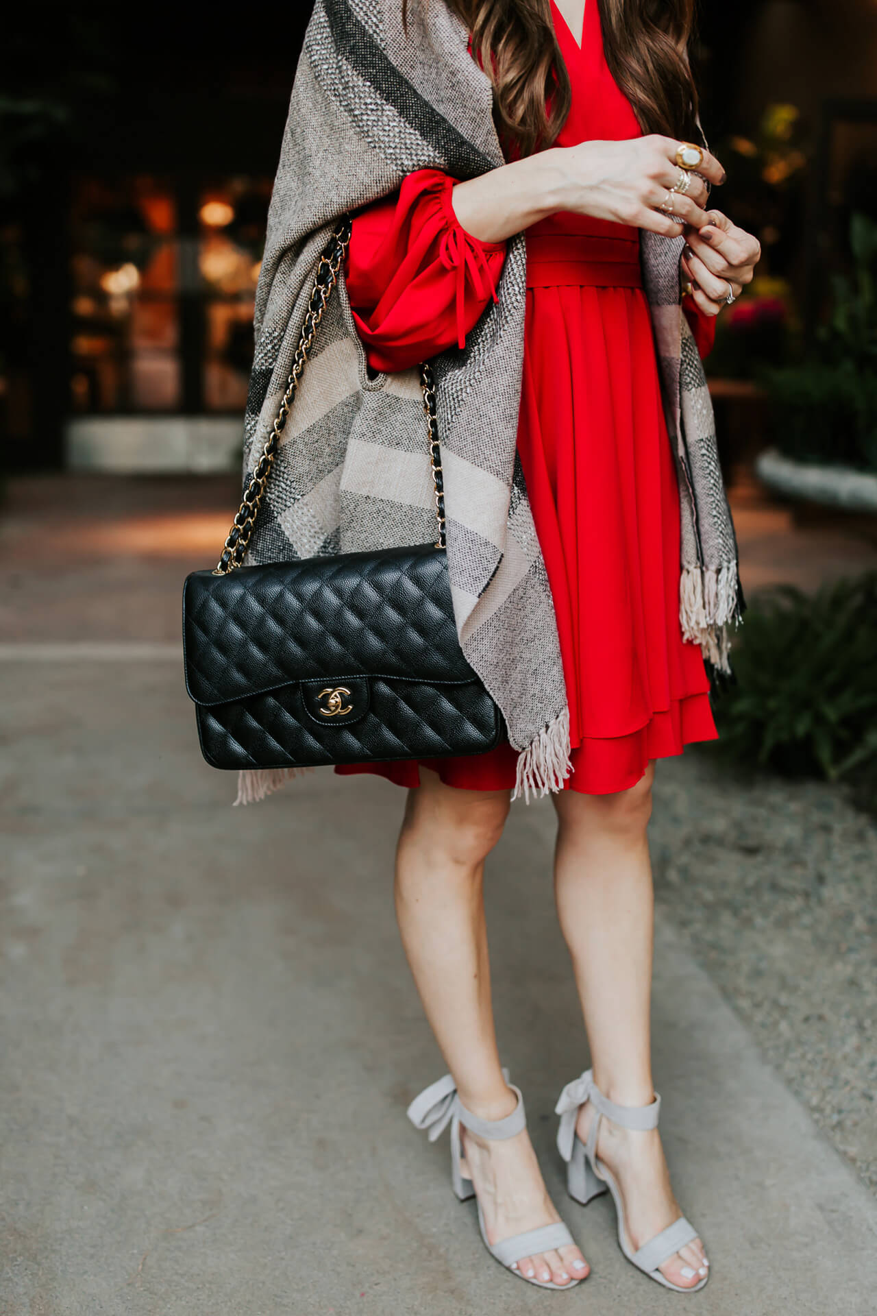Toning down this bright dress with a black bag and neutral poncho