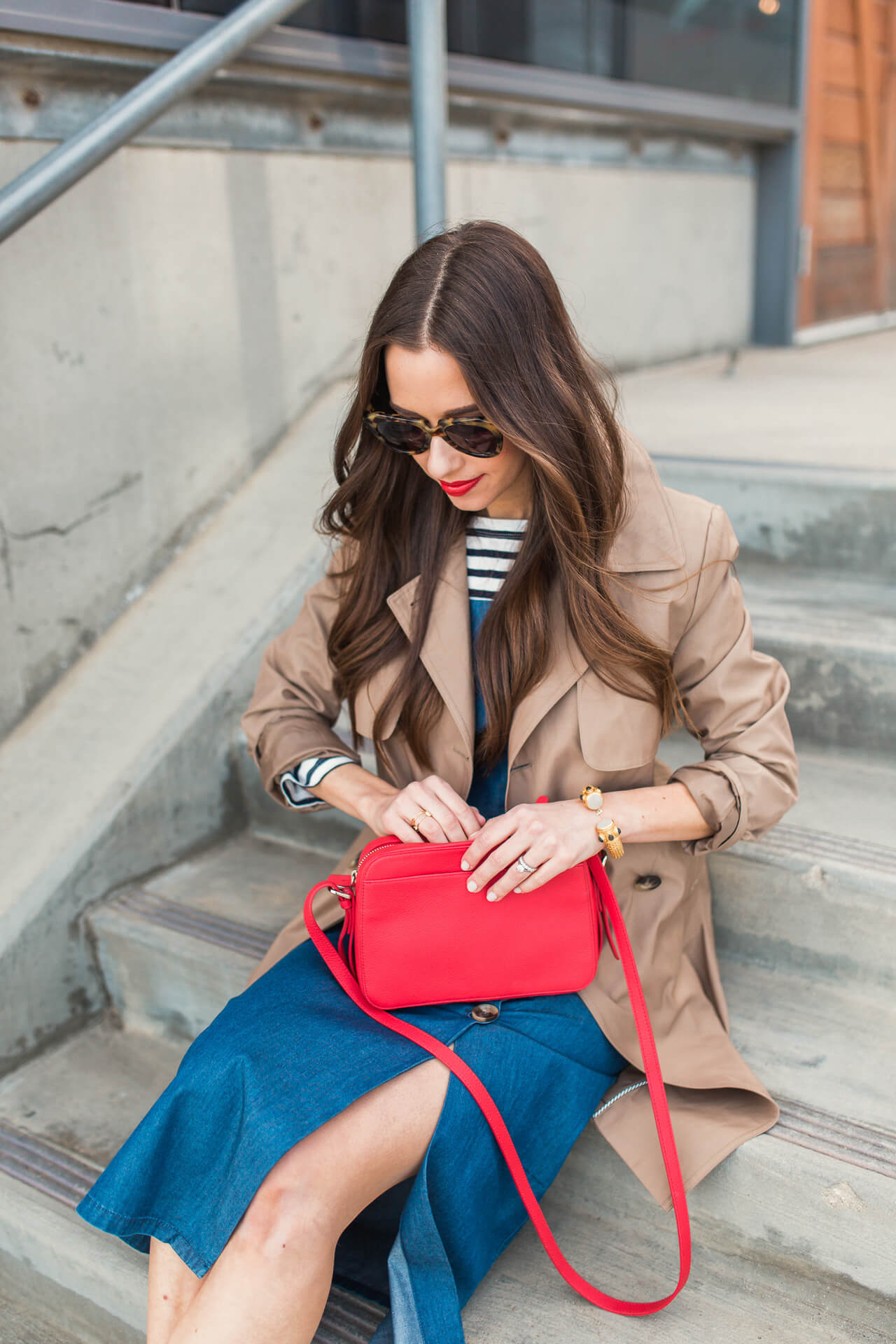 a cute rainy day outfit with a trench coat and denim dress and red bag - M Loves M
