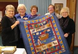 ladies from Audubon displaying quilt
