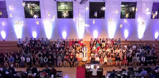 King of Grace students seated on bleachers for Christmas program