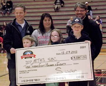 Luk Blackwell and Shawn Waller of Harris Ford-Lincoln present a check to Melissa Reid, MTHS Sports Booster Club Immediate Past President. (Blackwell's kids are in the front row.)