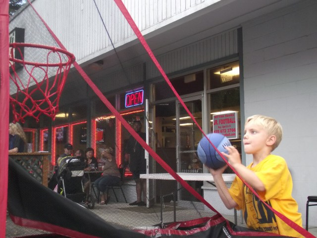 Jamie Moore, age 6 of Lake Forest Park, tries out the basketball shoot at the 44th Street Community Block Party on Saturday