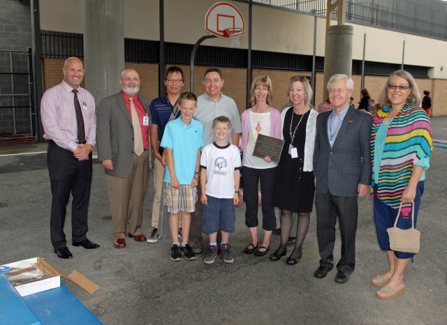 From left (back row) - Edmonds School District Superintendent Dr. Nick Brossoit, Facilities Director Brian Harding, Capital Projects Manager Nick Chou, Noel Baca, Kim Baca, Terrace Park Principal Mary Freitas, Board members Gary Noble and Ann McMurray, along with (front row) Baca's two sons Ryan and Kyle