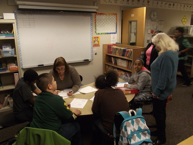 Retired teacher Meg Healas helps some of the students with their math.