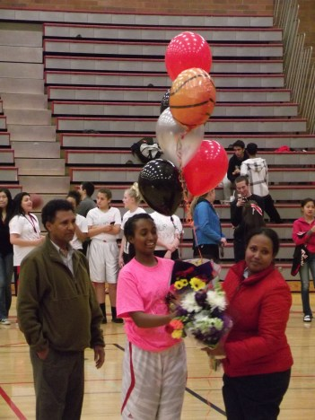 Senior Senaiet Zerom, shown with her parents, sang the National Anthem before the start of the game. (Photo by Doug Petrowski)