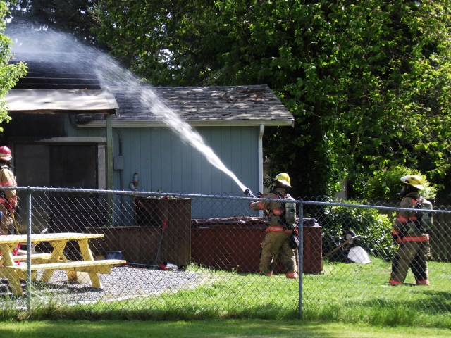 Firefighters douse hot spots at the rear of the house.