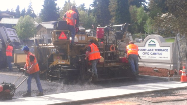 Work crews spent Tuesday paving the newly-rebuilt and reconfigured parking lot outside the Mountlake Terrace Library. The parking lot has been closed since January as the city had built an underground stormwater detention facility at the site. A portion of 58th Avenue West was closed on Tuesday due to the work, and is expected to be affected again on Wednesday. A detour route is marked for drivers in the area; the library is open regular hours, with parking available in a lot to the east of 58th Avenue West. (Photo by Doug Petrowski)