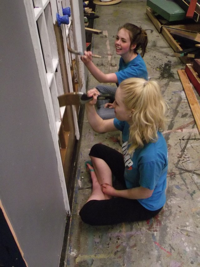 Amanda Petrowski (foreground) and Mikayla French paint doors that will part of the large set. Both students have on-stage roles in the comedy.
