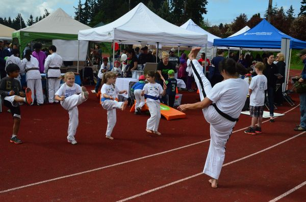The annual Edmonds Fitness Expo organized by Edmonds Parks and Recreation attracted more than 50 local businesses and hundred of visitors Saturday morning at Edmonds Stadium. Visitors to the Bailey's Taekwon Do booth got the chance to try on the uniform and get instruction in some basic Taekwon Do moves from teacher Nikka Gaviola. (Photos by Larry Vogel)