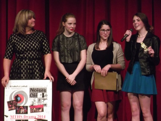 MTHS drama department head Jeannie Brzovic is presented with a mounting of 2013-2014 memories by students of the drama department at their awards ceremony Tuesday night. Pictured with Brzovic are (left to right) Cassie Stires, Emily Davidson and Mikayla French.