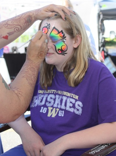 Ella Sundell patiently waits as Melissa Gallardo Plourd finishes painting her face.