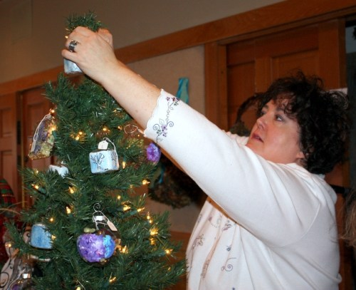 Dever Dunnett, owner of Micro Angelo Design, decorates a tree with some of her handmade ornaments.